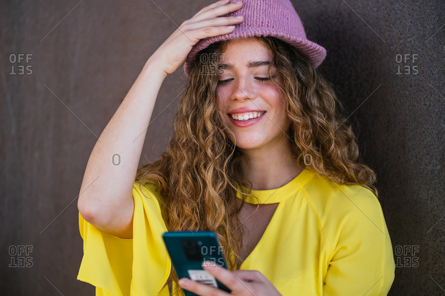 Delighted woman adjusting stylish hat while using smartphone