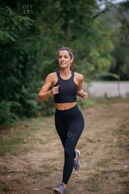 Young sportswoman running on park during outdoor workout.