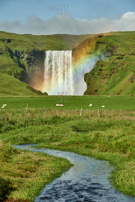 Breathtaking waterfall with rainbow and creek in valley