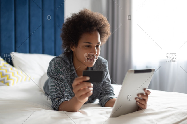 Ethnic female paying for online purchases on tablet