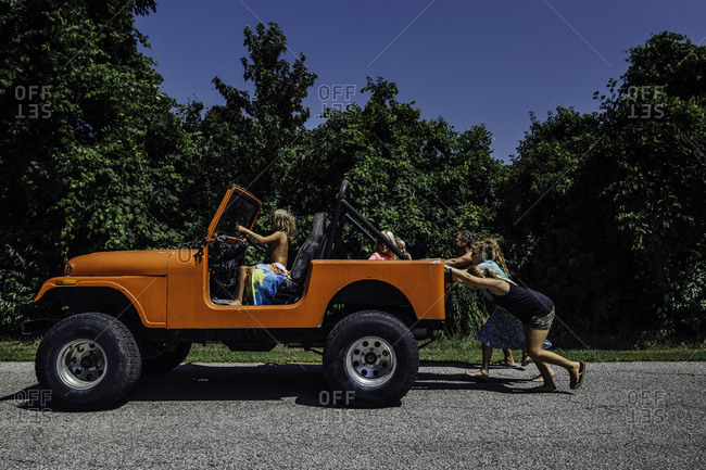 Family pushes orange jeep while young child steers