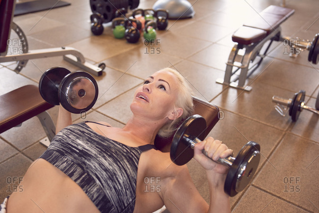 Fit woman doing bench press workout with dumbbells