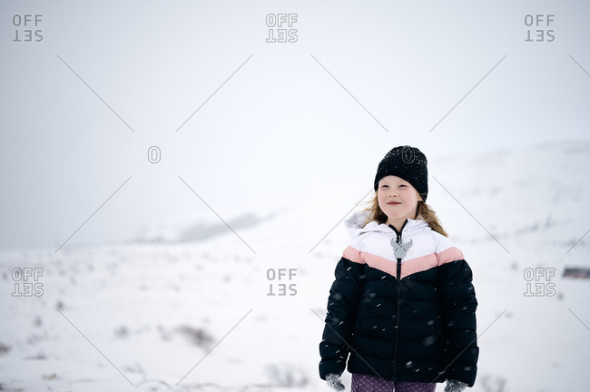 Positive cute kid enjoying winter day in mountains