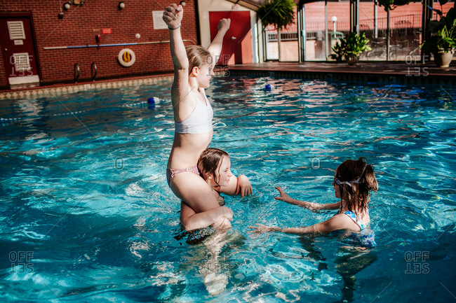 Three girls playing in an indoor swimming pool