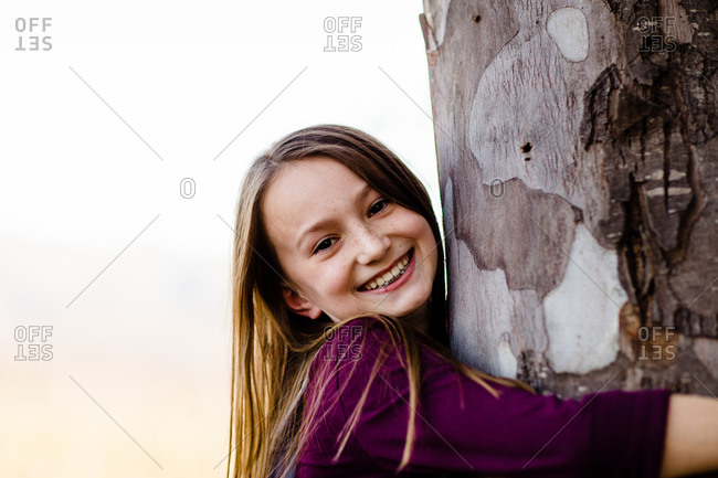 Young Girl Smiling for Camera & Hugging Tree