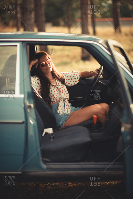 Woman in car smiling and looking at camera.
