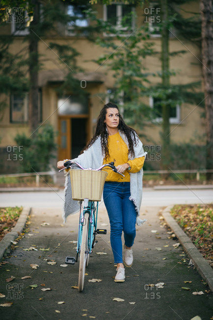 Young woman with her bicycle on the street.