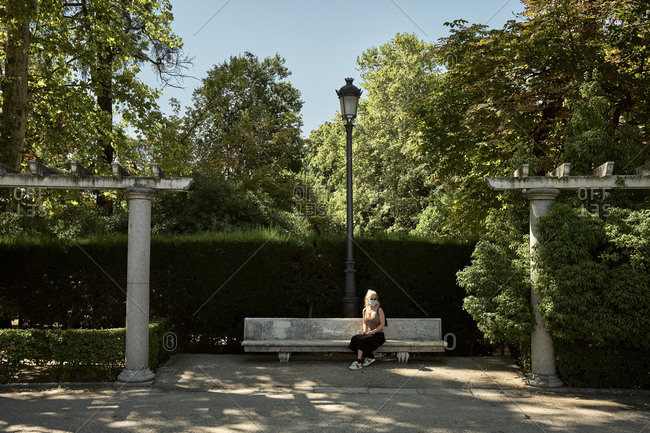 Woman in mask sitting on bench in park