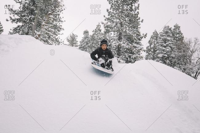 Boy Starts Down Snowy Hill on a Sled.