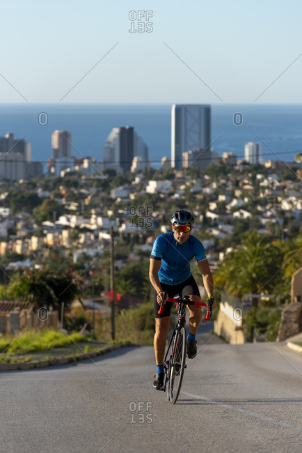Cyclist climbing around Calpe village with mediterranean sea behind.