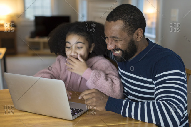 African-American father and tween daughter laugh looking at laptop