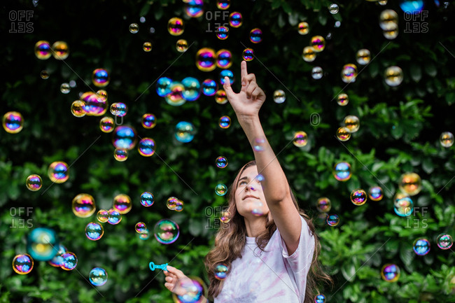 Teenager Points Up While Surrounded by Iridescent Colorful Bubbles