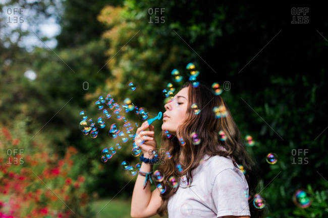 Teenager Blows Bubbles Outdoors with Iridescent Colors & Activity