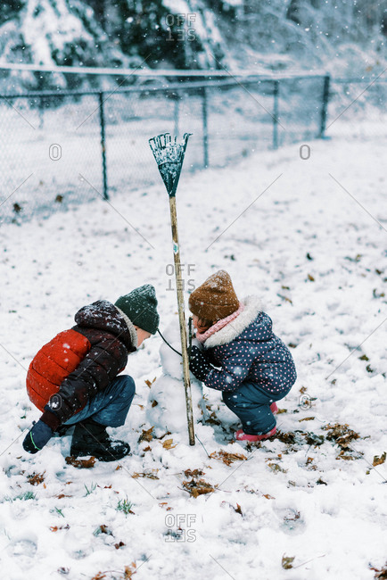 Two children making snowman together during snowfall in backyard