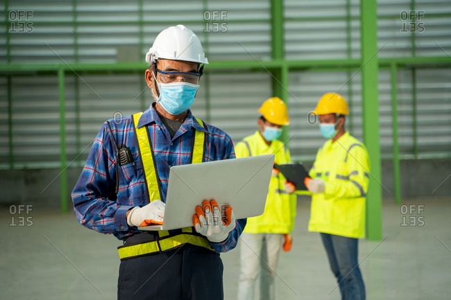 Warehouse worker wearing protective mask to Protect Against Covid