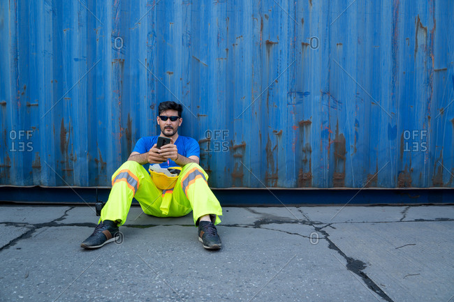 Containers worker sitting at container cargo area, feeling sad an