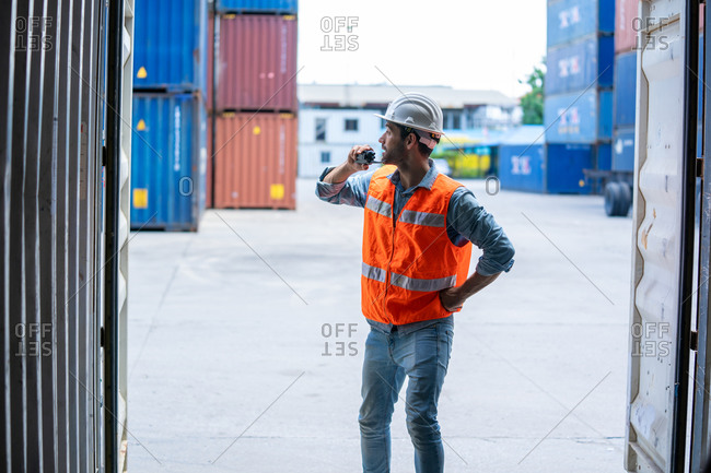 Container worker talking on the walkie-talkie at container warehouse