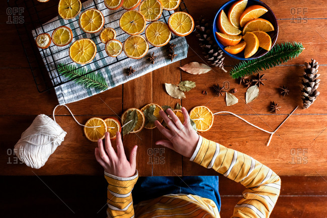 Childs hands putting together dried orange garland for Christmas