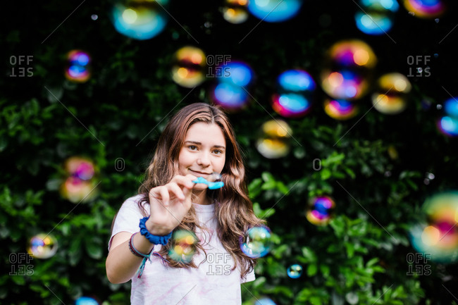 Teenager Catches a Bubble While Surrounded by Iridescent Color