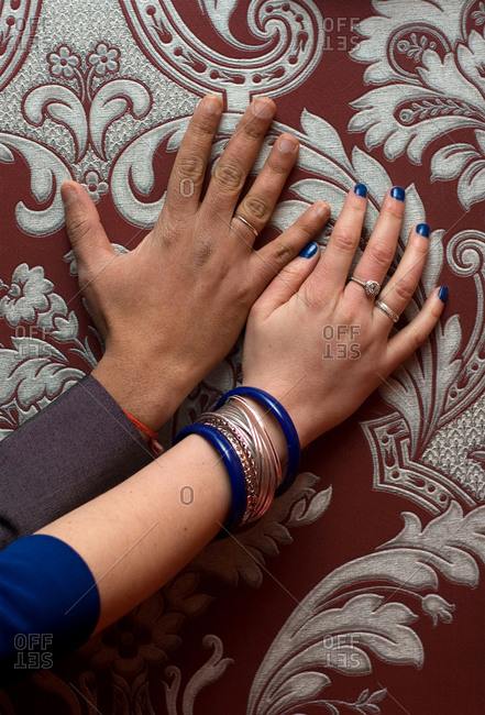 Just married multiracial couple hands with rings on wallpaper