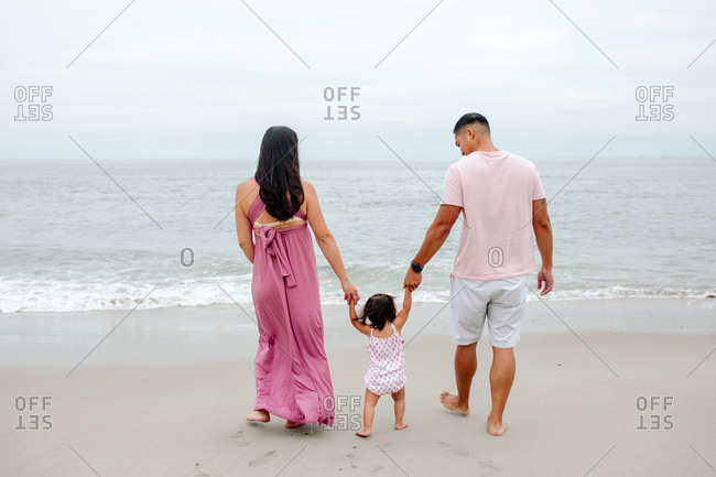 Barefoot parents with toddler walking on beach toward ocean
