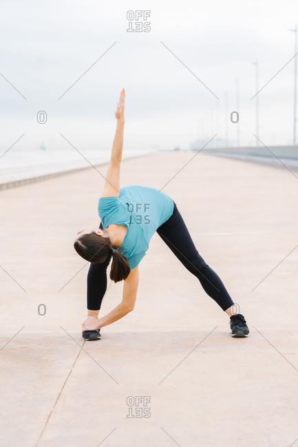 Girl practicing yoga extended triangle pose on the street