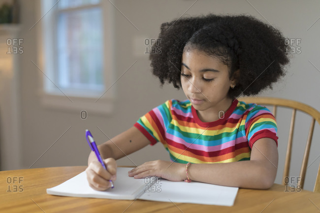 Ten year-old bi-racial girl writing in notebook at table