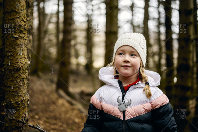 Positive child in warm clothes relaxing in autumn forest