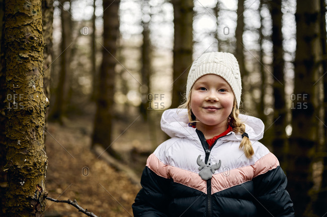 Content little girl chilling in autumn forest in daytime