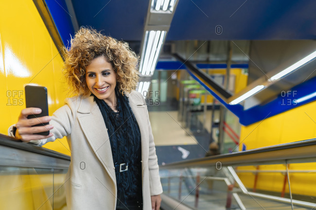 woman going up the escalator while using her smartphone