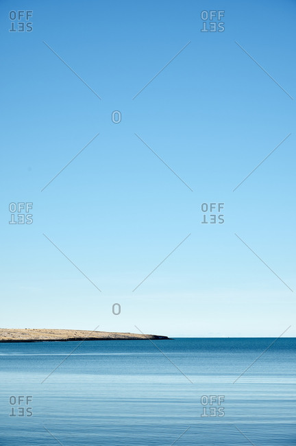 Peaceful blue sea with rocky coast under cloudless sky