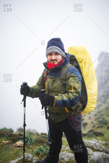Hiker standing and looking at camera during foggy day