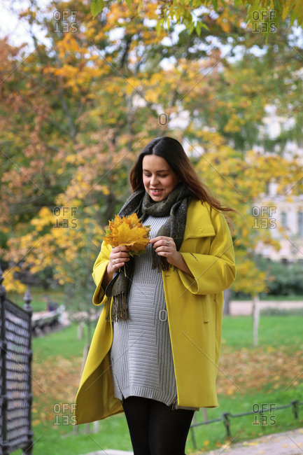 Image of a happy pregnant woman outdoors in autumn.