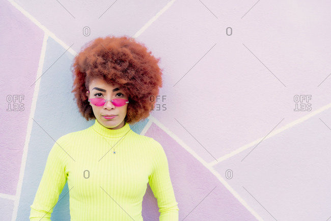 portrait of woman with afro hair and pink glasses