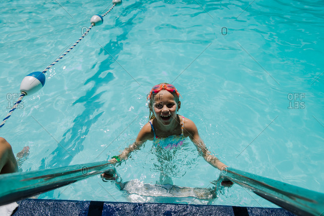 Little Girl Looking up from Pool Ladder in water