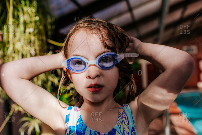 Young Girl putting on goggles at a swimming pool