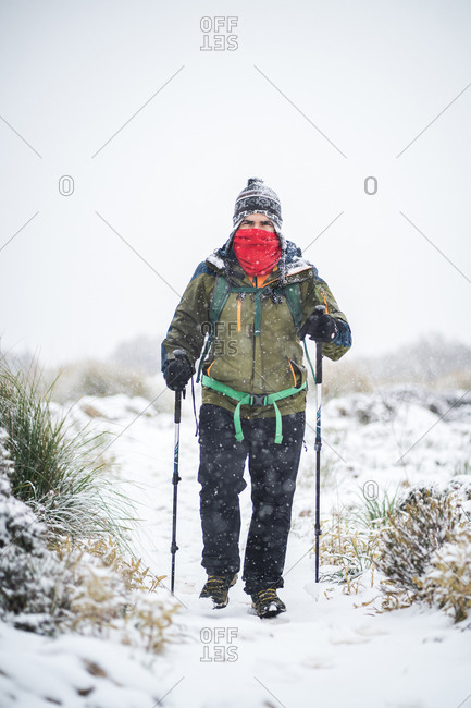 A man with face covered treks under heavy snow