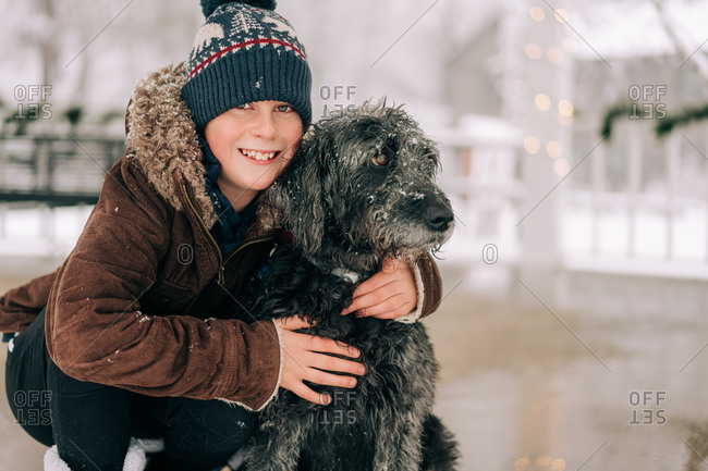 boy hugging his dog on a snowy winter day