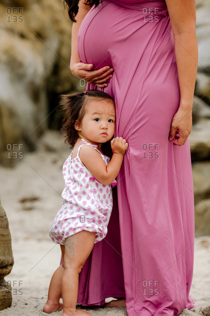 Precious Asian toddler clings to mother's dress beneath pregnant belly