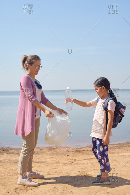 Daughter and mother collected plastic bottles by the lake together