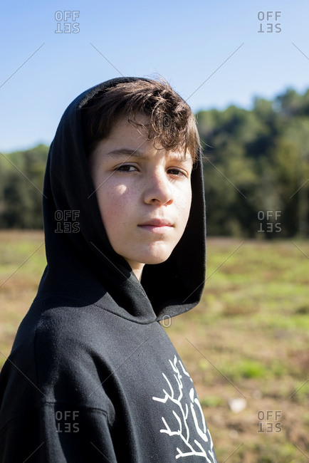 Outdoor handsome boy portrait in hood over park nature background.