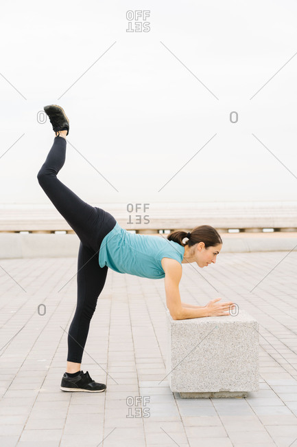 girl practicing yoga on the street. Doing glute exercises. Pilates