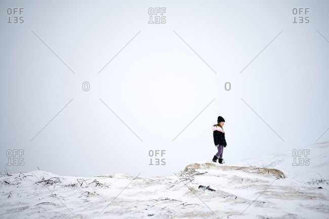 Unrecognizable kid in warm clothes walking on snowy mountain slope