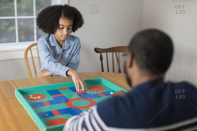 African America ten year-old girl playing board game with father