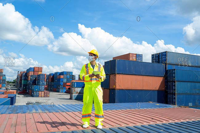 Young worker man with digital tablet at container terminal port,
