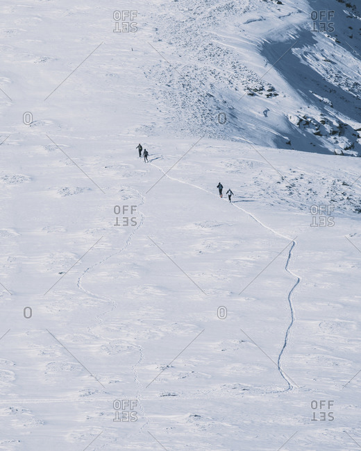 Group of backcountry skiers going up hill, against mountain peak