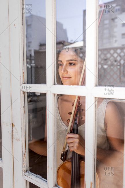 Young girl through a window while holding a musical instrument.