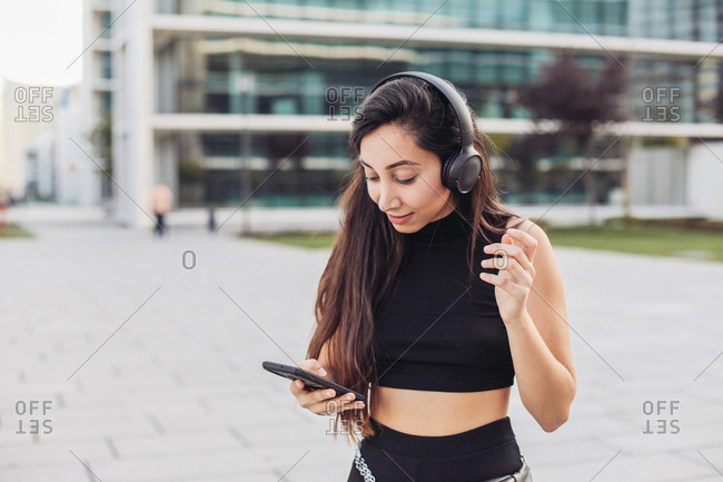 Young woman in black with headphones looking at her smartphone