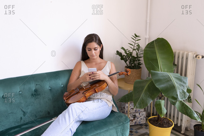 Sitting girl chatting with her cellular while holding a viola.