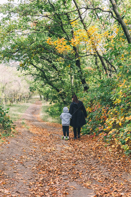 Woman hold little boy driving scooter at beautiful autumn path